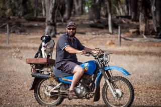 Photo of Roger on a motorbike on the farm, with the farm dog.