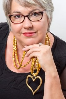 Photo of Caro Telfer, woman wearing glasses, a black dress, and a large heart necklace