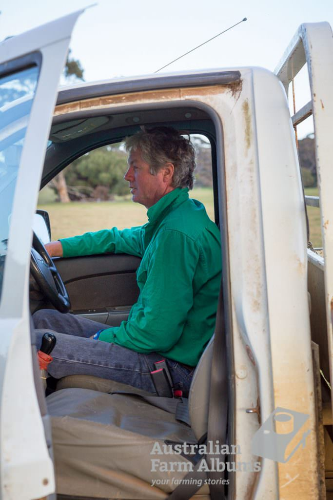 Photo of farmer wearing a green shirt sitting in a white farm ute