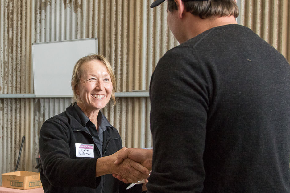 photo of smiling woman shaking hand of buyer