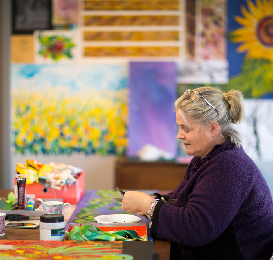 photo of lady artist working in art studio
