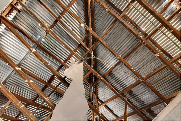 Photo of a roof showing wooden beams, tin roof, and fallen ceiling