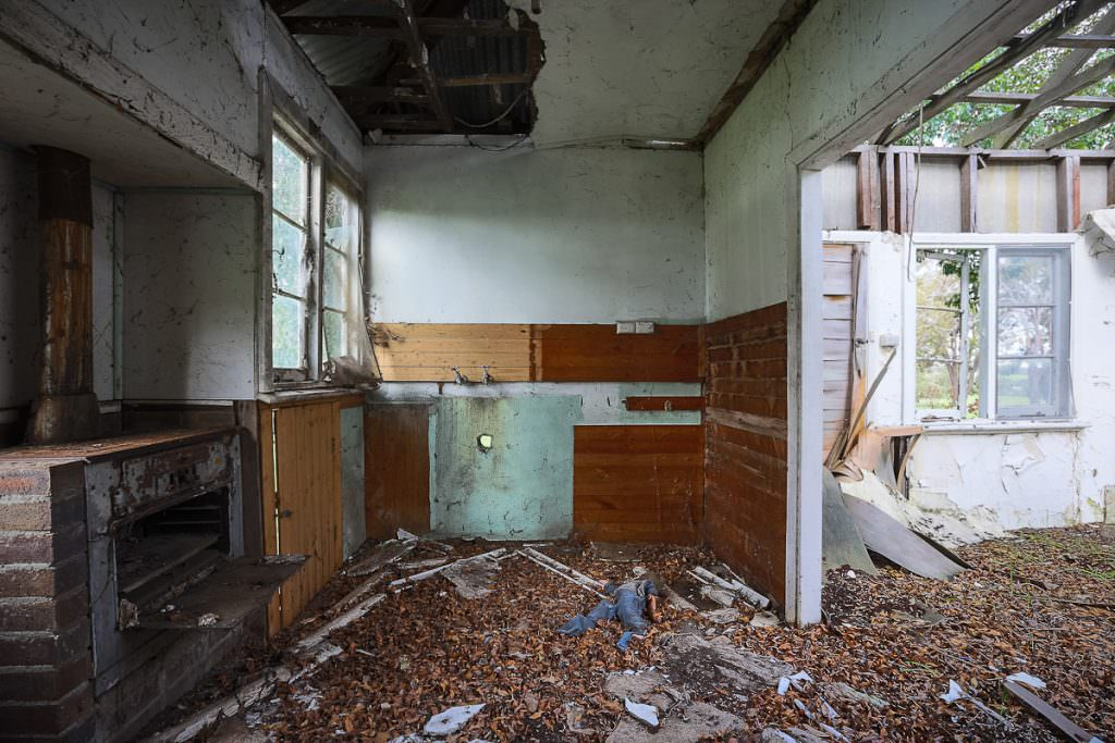 Photo of a derelict farmhouse kitchen with old wood stove, leaf debris and no roof